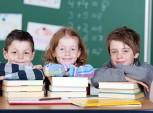 três crianças com pilhas de livros dentro de sala de aula