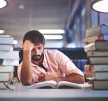 rapaz numa biblioteca estudando entre pilhas de livros.