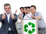 Grupo de funcionários fazendo sinal de positivo e depositando papéis numa caixa para reciclagem.