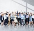 grupo de funcionários sorrindo e levantando as mjãos