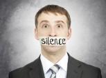 homem com a boca tapada com a palavra silêncio