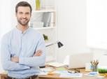 homem sorrindo encostado numa mesa de trabalho.