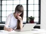 mulher senta à frente do notebook fazendo anotações