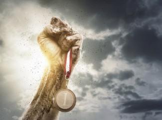 mão para o alto segurando uma medalha