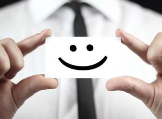 homem segurando uma papel com o desenho de um rosto feliz