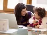 mulher trabalhando e brincando com a filha