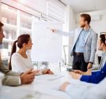 foto de homem mostrando quadro em reunião para funcionários