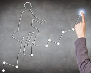 foto de mão em cima de desenho de gráfico com homem subindo