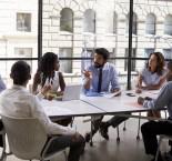 foto de pessoas sentadas conversando em volta da mesa