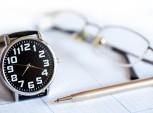 mesa de trabalho com relógio, caneta e planilha