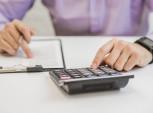 foto de pessoa mexendo na calculadora e escrevendo no papel
